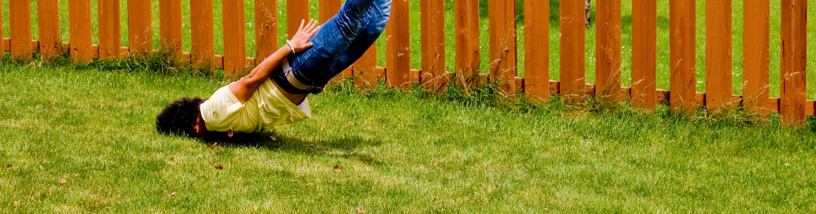 A guy does a faceplant in the grass.